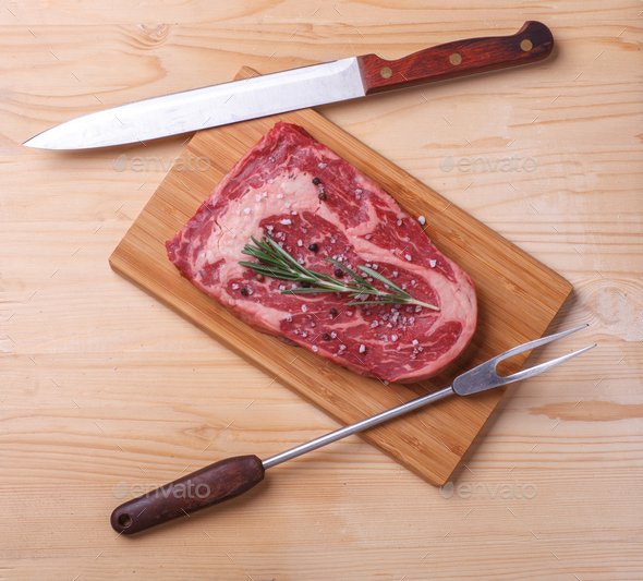 raw uncooked marble beef steak ribeye with knife and cook fork - Stock Photo - Images