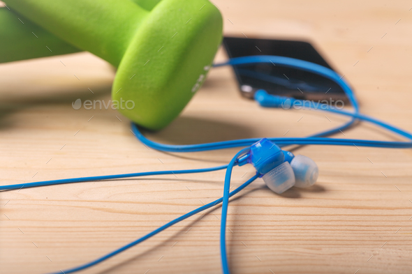 earphones on wooden table with blurred dumbbells and smartphone - Stock Photo - Images