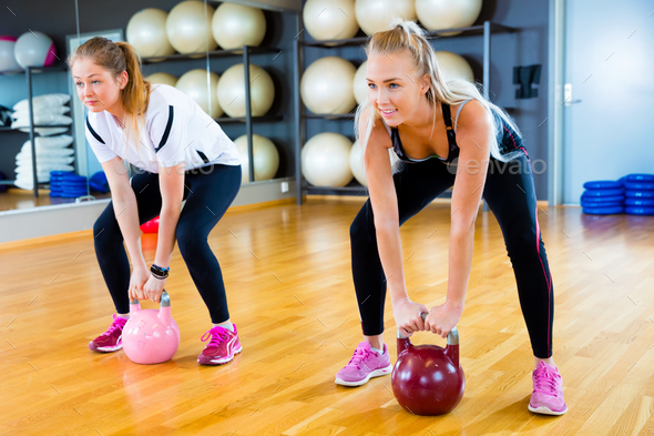 Determined Friends Lifting Kettlebells In Fitness Center - Stock Photo - Images