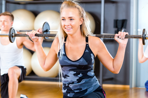 Close-up of Young Woman Lifting Barbell Rod With Friends In Gym - Stock Photo - Images