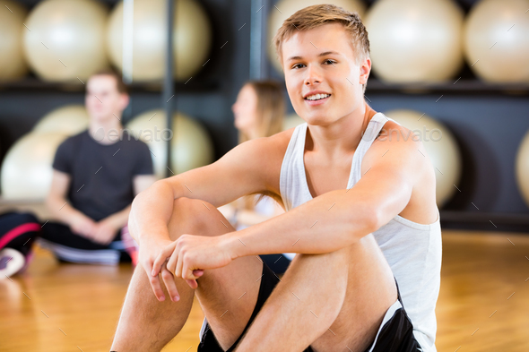 Confident Man Sitting In Fitness Studio - Stock Photo - Images