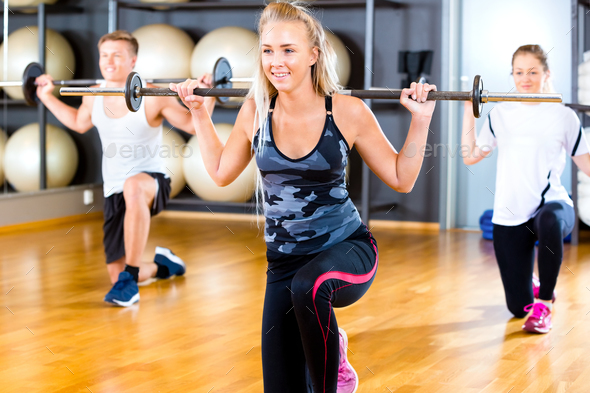 Young Woman Lifting Barbell Rod With Friends In Gym - Stock Photo - Images