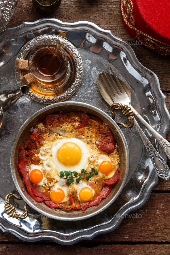 Turkish cured beef and fried eggs in copper pan, traditional breakfast, top view - Stock Photo - Images