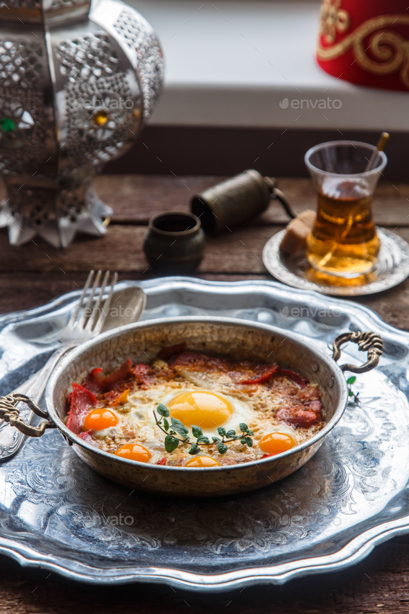 Copper pan with fried eggs and sausages, turkish style - Stock Photo - Images