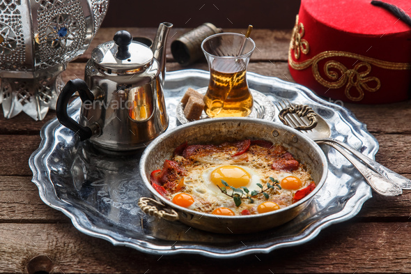 Fried egg with cured meat, traditional turkish breakfast, served in metal dishware, rustic - Stock Photo - Images