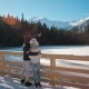 Young Couple Is Standing Near Mountain Lake in Winter Looking at Landskape - VideoHive Item for Sale