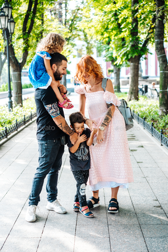 Happy beautiful family walking in the park - Stock Photo - Images