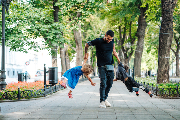 Children having fun with dad in the park - Stock Photo - Images