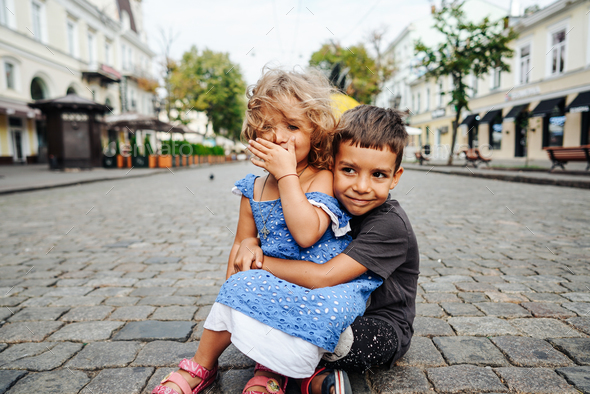 little boy and girl are sitting on the street - Stock Photo - Images