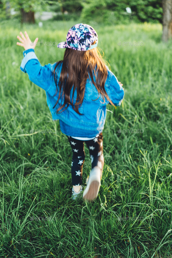 little, beautiful girl on the lawn - Stock Photo - Images