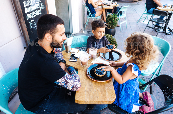 Dad, daughter and son are eating dessert - Stock Photo - Images
