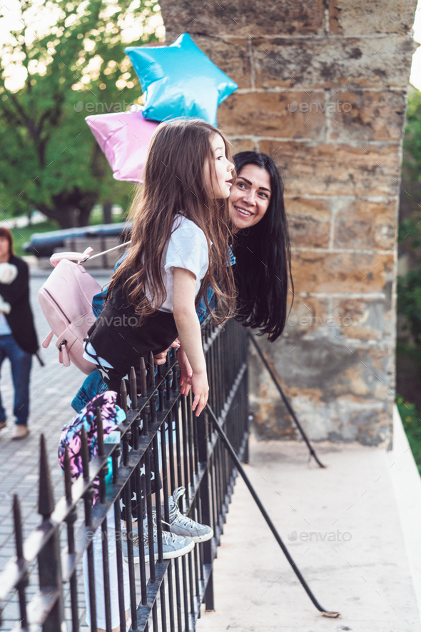 preschool girl and mother at the fence - Stock Photo - Images