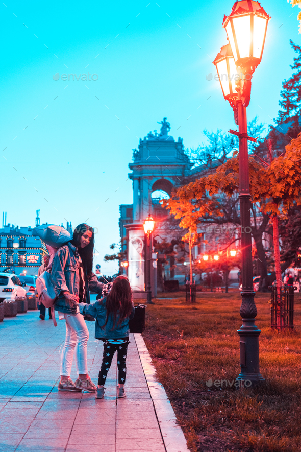preschool girl and mother in the evening city - Stock Photo - Images