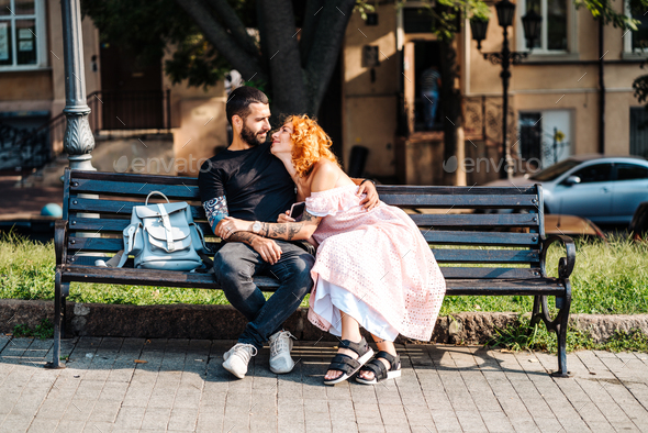 Beautiful dating couple hugging on a bench - Stock Photo - Images