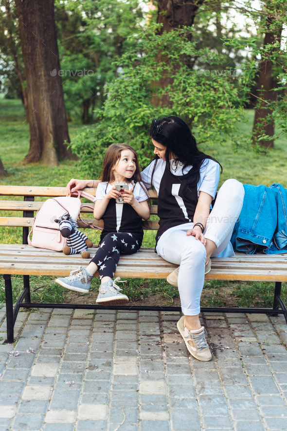 mom and daughter rest on the bench - Stock Photo - Images