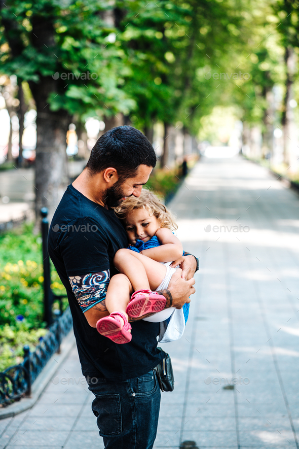 Cute little girl in her father's arm - Stock Photo - Images