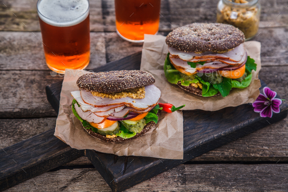 Homemade sandwich with ham, onion, tomato, cheese and mustardon rustic background - Stock Photo - Images