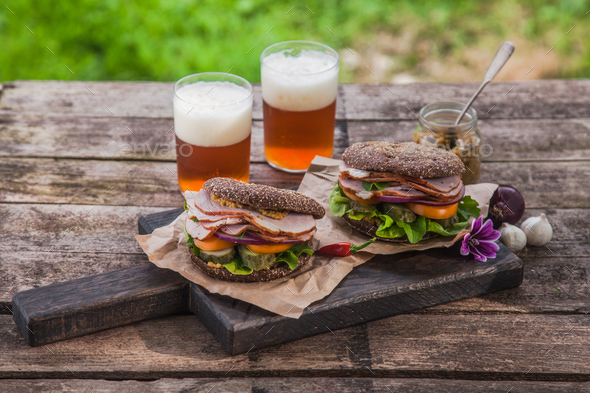 Homemade sandwich with ham and a glass of beer on an old background - Stock Photo - Images