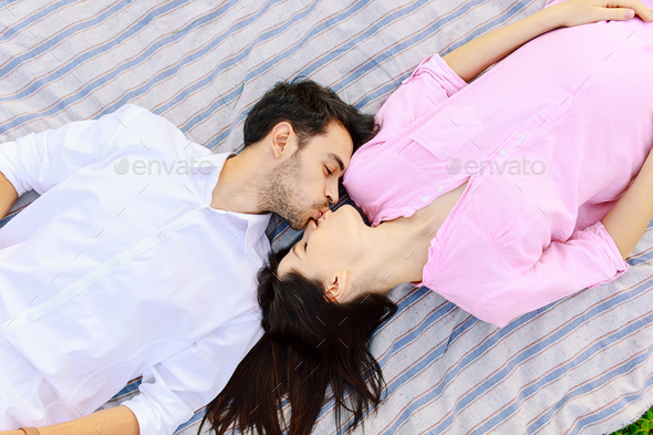 Enjoying closeness top view of beautiful young loving couple lying together. - Stock Photo - Images