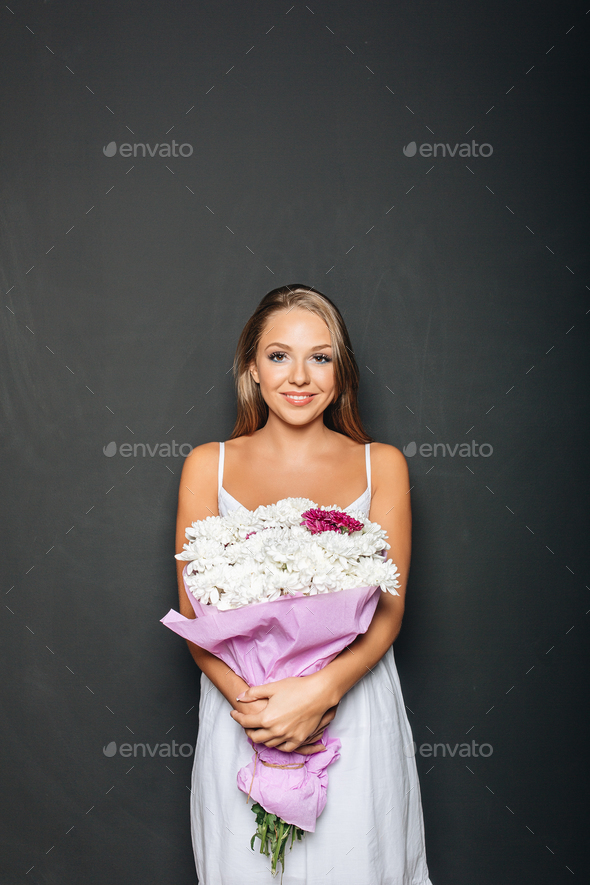 Beautiful woman holding bunch of flowers - Stock Photo - Images