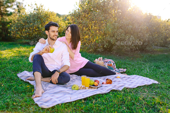 Young Couple in The Park Outdoors having a picnic - Stock Photo - Images