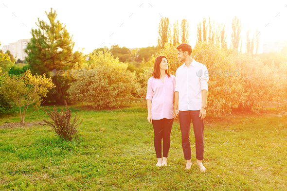 Portrait cheerful pregnant couple in the park - Stock Photo - Images