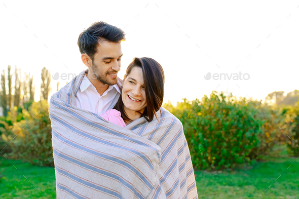 Happy couple portrait wrapped in a blanket - Stock Photo - Images