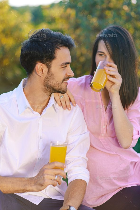 Happy couple drinking orange juice in the park looking to each o - Stock Photo - Images