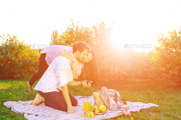 Happy couple having a picnic in park on a sunny day, kissing and hugging - Stock Photo - Images