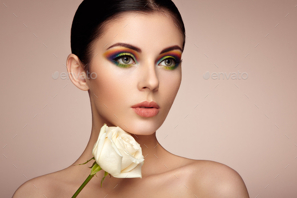 Portrait of beautiful young woman with rainbow make-up - Stock Photo - Images