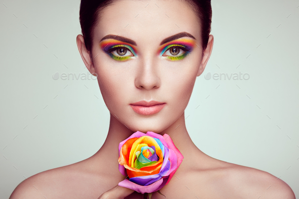 Portrait of beautiful young woman with rainbow rose - Stock Photo - Images