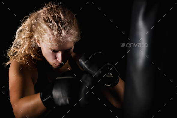 Young Women Hitting Boxing Bag - Stock Photo - Images