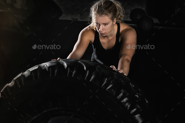 Young Woman Flipping Heavy Tire - Stock Photo - Images