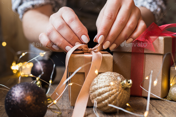 A woman holding a Christmas gift with a ribbon on a wooden table. Christmas presents and New Year - Stock Photo - Images