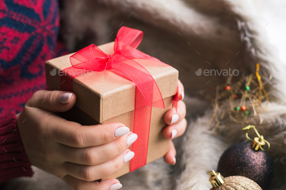 A woman holding a Christmas gift with a red ribbon on a wooden table. Christmas presents - Stock Photo - Images