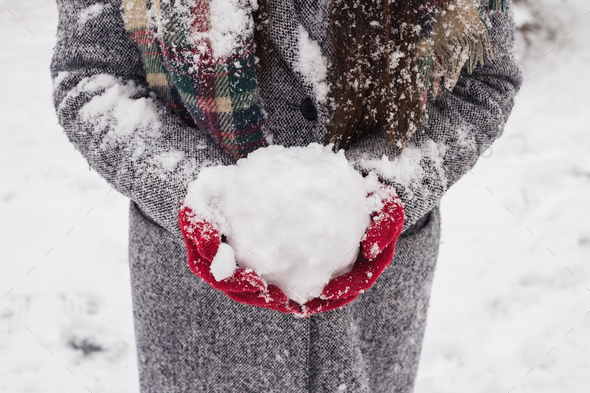 Girl wearing red covered gloves holding snow with Merry Christmas greeting - Stock Photo - Images