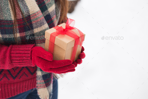 A girl holding a gift in her hands on the street in winter - Stock Photo - Images