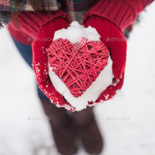 Hands in woolen mittens holding red heart - Stock Photo - Images