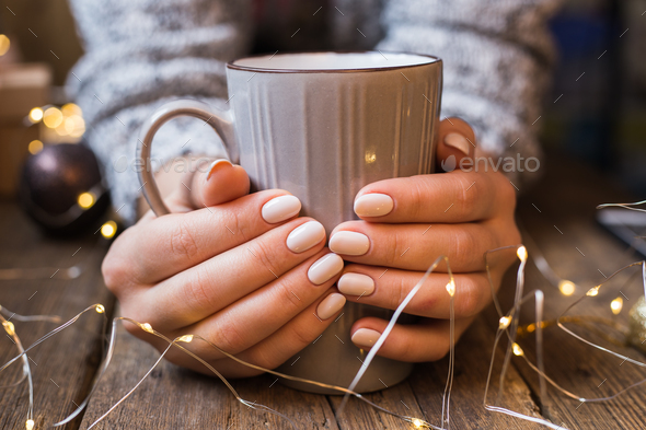 Female hands holding a cup. New Year or Christmas card - Stock Photo - Images