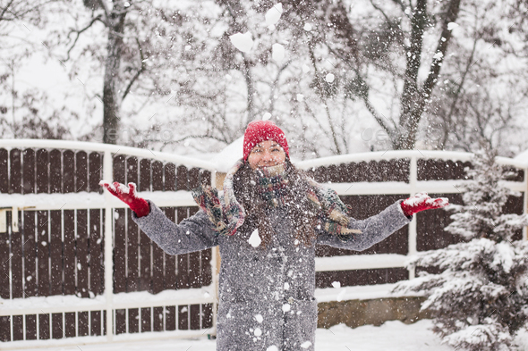 A girl stands against the background of winter and throws snow. - Stock Photo - Images