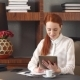 Stylish Redhead Girl Working at Home Office.