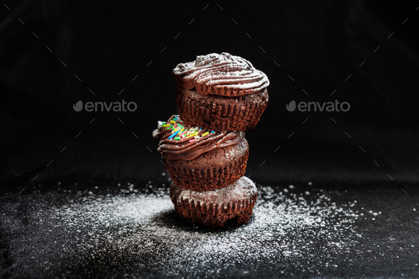 A pile of cup cakes on a black background - Stock Photo - Images