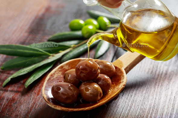 Wooden spoon with olives and olive oil - Stock Photo - Images