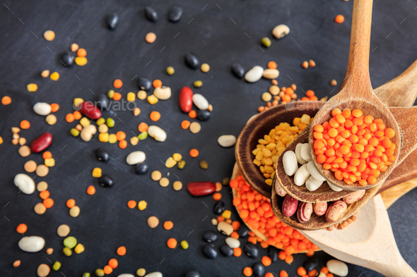 Various raw legumes in wooden spoons - Stock Photo - Images