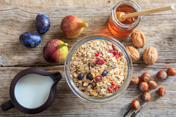 A bowl with muesli, fruits and nuts on a wooden table - Stock Photo - Images