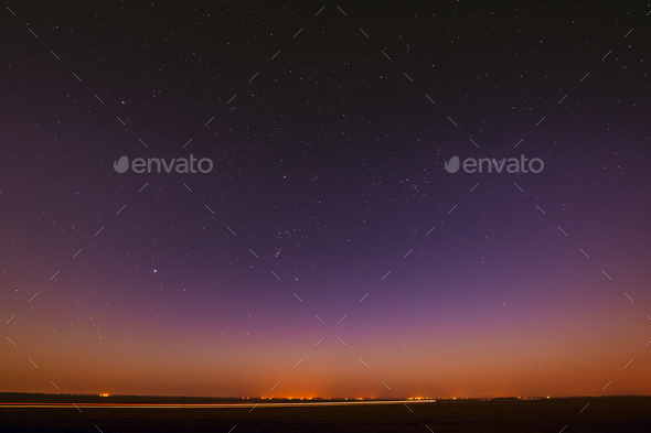 Night Starry Sky Over Yellow Sunset Or Sunrise Lights. Night Glo - Stock Photo - Images