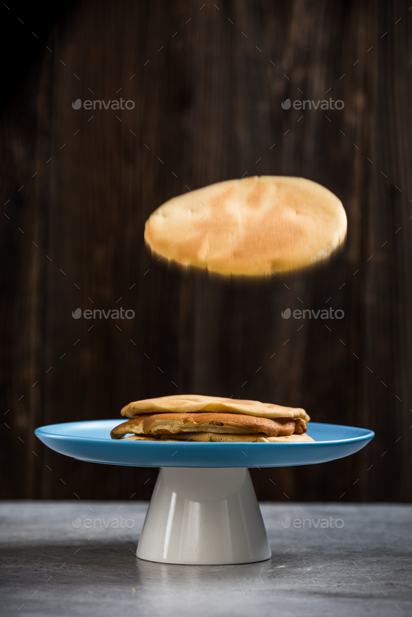 Pancake flying into plate - Stock Photo - Images