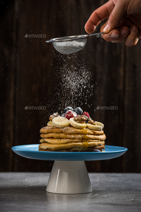 Sprinkling pancakes stack with sugar powder - Stock Photo - Images
