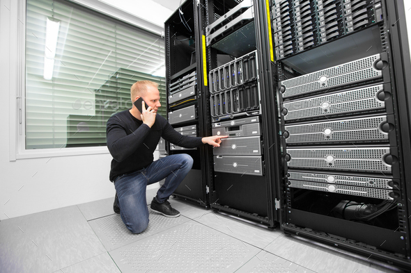 Consultant Using Smartphone While Monitoring Servers In Datacent - Stock Photo - Images