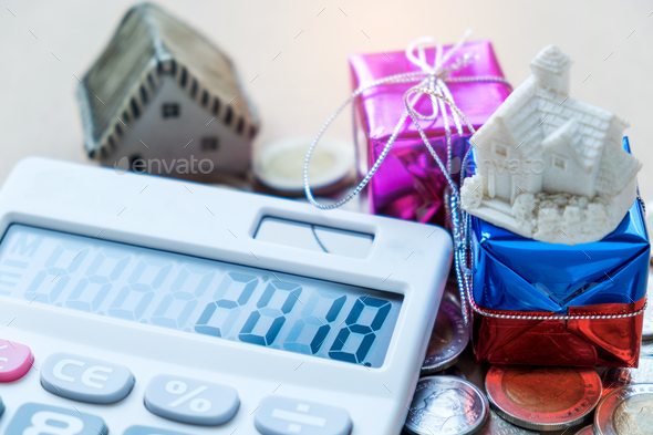 2018 Number on calculator display,house model and gift place on coins. - Stock Photo - Images